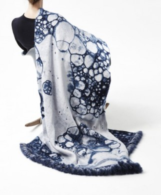 deel van mens op de rug gezien, zwart shirt, kleed over rechter schouder, wit met blauwe bubbelachtige vormen