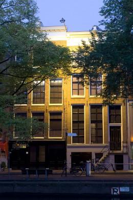 Okergele gevel van een huis, frontaal sangezicht, ramen met zwarte ruitdelen, Blauwe lucht, aan weerzijden gevel, twee groene boomkruinen