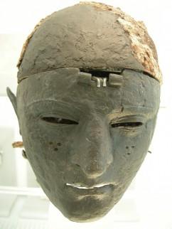 IJzeren Romeinse gezichtsmasker, de drie gaatjes op de wang stellen een tatoeage voor. In het midden restanten van het scharnier waarmee het masker aan de helm vastzit. De helm had een overtrek van bont (haren van mensen of beren).