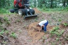 Bruine bodem, groene boemen, traktor zwart en rood, man, wit en blauwe kleding