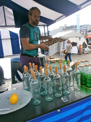 standje blauw groen wit, groene flessen en man in groenblauw T-shirt