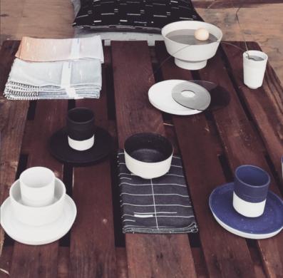 bruin tafelblad met links wit kop en schotel, rechts een blauwe. Linksboven grijze en beige theedoelen., linksboven een schaaltje.