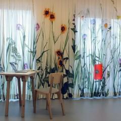 Hoge houten tafel met ernaast stoel, tegen achtergrond, wit gordijn met kleurrijke bloemen op hoge groene stelen