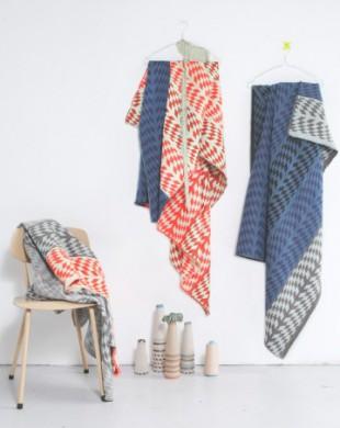 links een stoel met kleden erover, met blauw/wit en oranje/wit patroon, Aan de muur, 2 klerenhangers met kleden, oramje/wit, blwu/zwart patroon