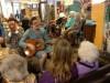 Vrouw met zeegroene blouse, met gitaar met mensen eromheen