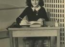 Meisje, frontaalm ziitend aan bureau, zwarte trui, witte kraag, pen in der echterhand, op tafel een wit schrift. Erachter zwarte tegels, witte geruite verwarmingselement, witte kan