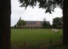 grijze strook met groen, rood gebouw, groen gras