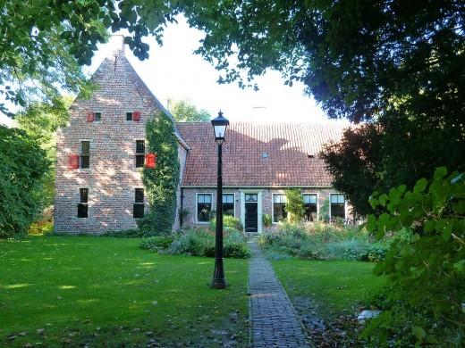 Gebouw in rode baksteen, blauwe lucht en groen gras