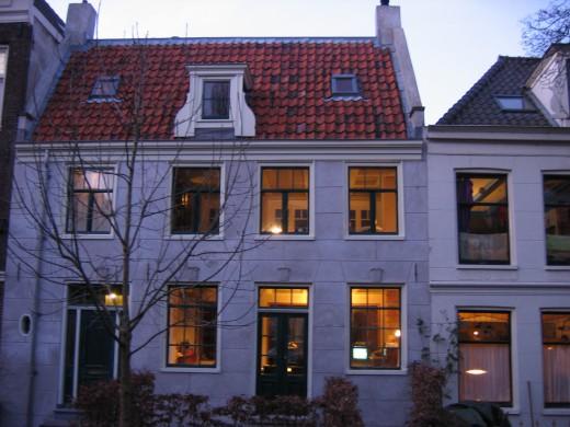 Witte huizen met rood dak, geel schijnsel door de ramen, witte lucht