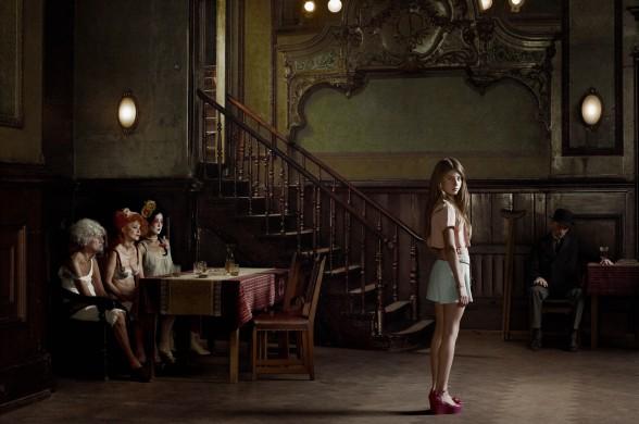 Bruin, groene wanden en vloer, vrouw mintgroene korte broek  en perzikroze naveltruitje, links aan tafel drie schaars geklede vrouwen van verschillende leeftijd en pluimage