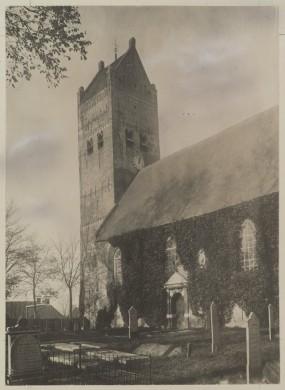 grijze en witte afbeelding, kerktoren en deel van de romp in grijs wit en zwart, bomen en witte grafstenen op de voorgrond