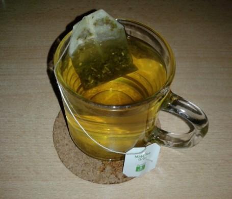stijlwit/grijze achtergrond, kop thee van bovenaf gezien met gele vloeistof erin