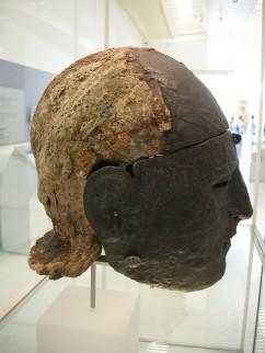 Zijaanzicht van een gezichtshelm. Op de helm zijn sporen van een geometrisch patroon van versieringen zichtbaar.