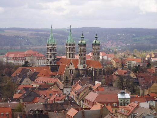 huizen en kerk met rode daken, achtergrond groen grijs landschap, grijze lucht