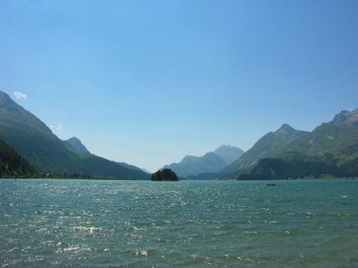 groen water voorgrond, blauwe lucht eracher, ertussen groene schuine berghellingen