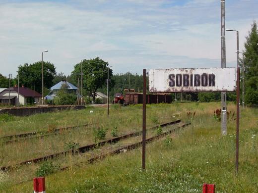 Groen landschap met wit bord Sobibor in zwarte letters