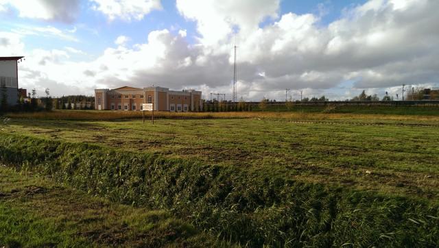 Groen grasveld, blauwe lucht, wit,grijze wolken, okergeel gebouw met witte lijsten