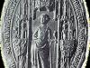 Grijze afbeelding, vrouw in lang geplooid gewaad, eromheen lijst meandermotieven