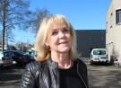 portret vrouw blond haar, zwart leren jack, tegen blauwe lucht, links auto's, rechts, beige gebouw