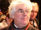 Man met bril, grijs haar, roze gezicht, daarachter nog een man met roze gezicht, tegen zwarte achtergrond